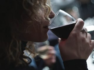 Woman drinking glass of wine. Castle Craig asks - can addiction be cured?