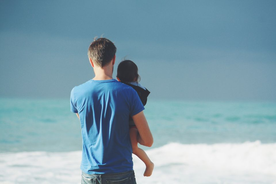 Dad holding child in front of the sea; a review of proactive parenting by Mandy Saligari, Castle Craig rehab