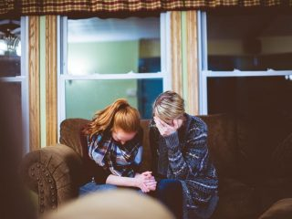 two women crying and holding hands; grief and addiction, Castle Craig rehab